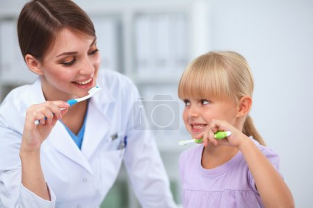 Dentist and little girl in the dentist office.