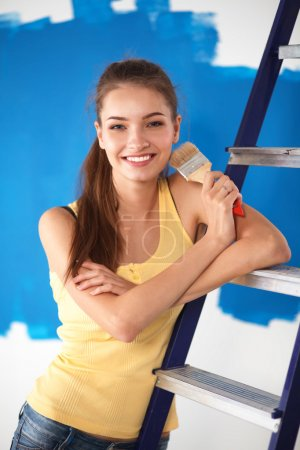 Happy beautiful young woman doing wall painting, sitting on ladder