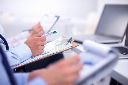 Photo pour Les gens d'affaires assis et écrivant lors d'une réunion d'affaires - image libre de droit