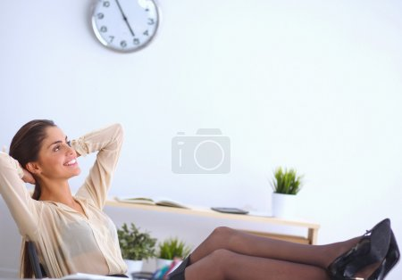 Business woman  relaxing with  hands behind her head and sitting on an office chair
