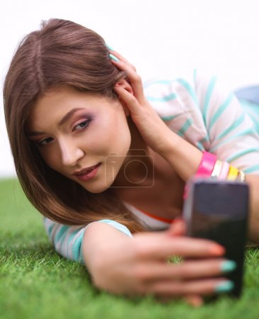 beautiful young woman making selfie by her phone while lying in green grass