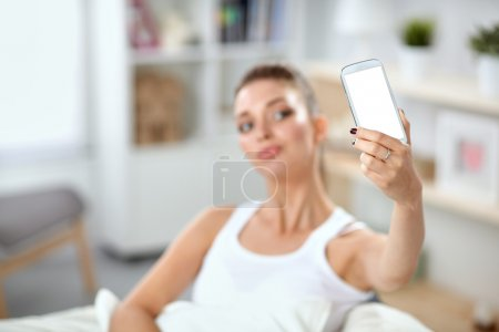 Happy brunette taking a photo of herself with her mobile phone in  bedroom