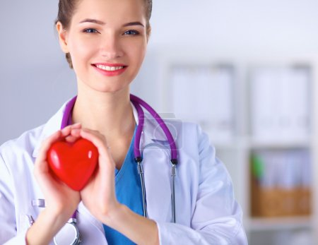 Young woman doctor holding a red heart, standing in hospital