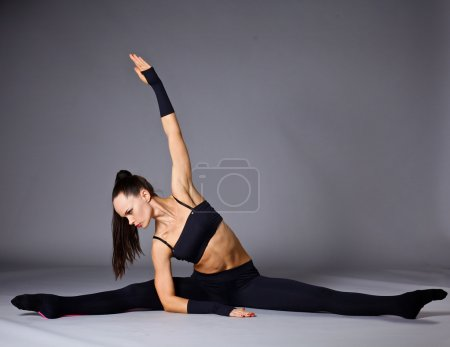 Young attractive female fitness woman performing a twine