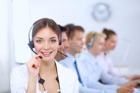Foto de Empresarios jóvenes positivos atractivos y sus colegas en una oficina del centro de llamadas - Imagen libre de derechos