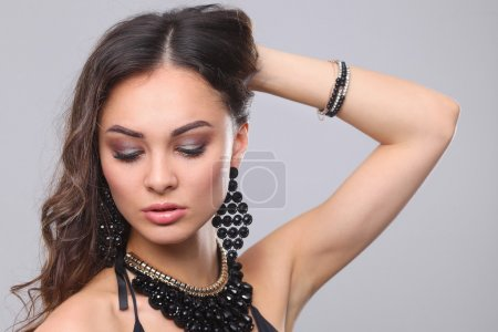Portrait of a beautiful woman with necklace, isolated on gray background