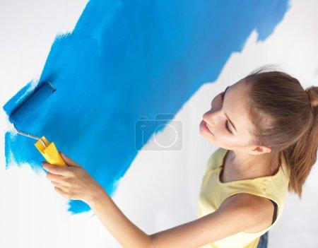 Foto de Hermosa mujer joven haciendo pintura de pared, de pie en la escalera - Imagen libre de derechos