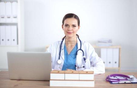Photo pour Belle jeune femme médecin souriante assise au bureau - image libre de droit