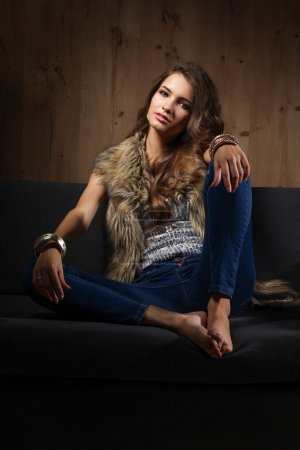 Photo for Portrait of a elegant woman sitting on a black sofa wearing a blue jeans and fur vest - Royalty Free Image
