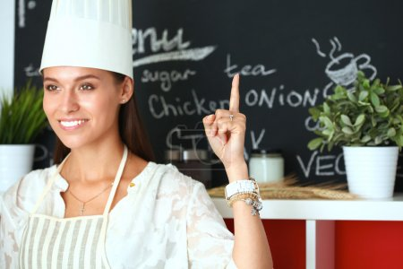 Photo for Chef woman portrait with  uniform in the kitchen and pointing up - Royalty Free Image