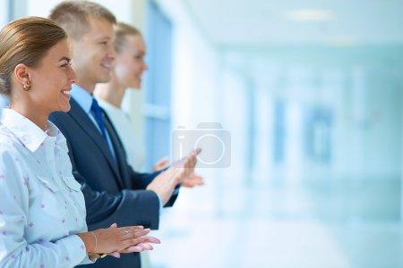 Photo pour Des gens d'affaires souriants applaudissant une bonne présentation au bureau - image libre de droit
