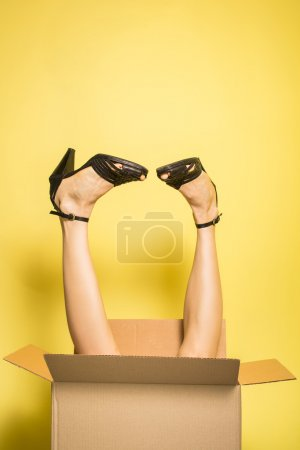 Photo for Funny shopping concept, woman legs sticking out from box over bright yellow background. copy space, soft studio shot - Royalty Free Image