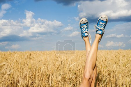 Photo pour Jambes femme sexy sur fond bleu ciel et champ de blé. Concept vacances d'été - image libre de droit
