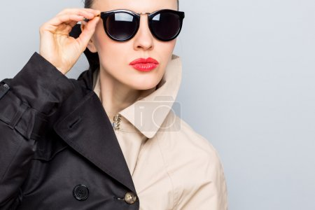 Stylish lady in sunglasses and rain coat