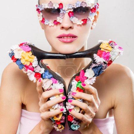 Fashion woman wearing sunglasses holding shoes