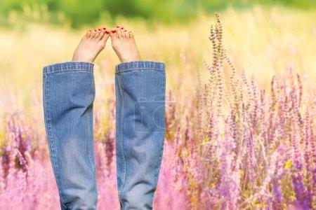 Photo pour Sexy femmes jambes pieds nus sur fond de prairie ensoleillée. Vacances d'été et concept de liberté - image libre de droit