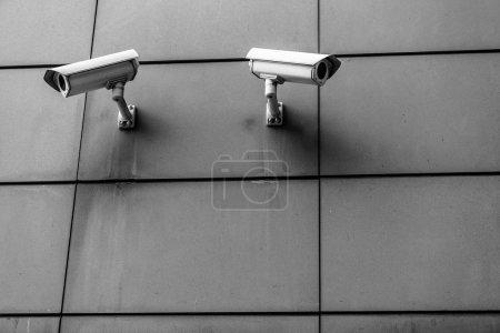 Photo pour Deux caméras de surveillance noir et blancs sur le mur en face de l'autre - image libre de droit