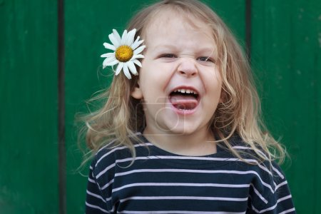 Head and shoulders portrait of two years old grimacing blonde girl with chamomile flower in her hair