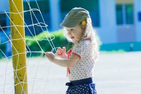 Nursery school girl playing near football goal net with yellow goalposts