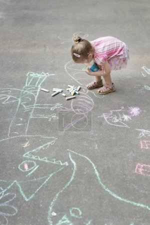 Overhead shot of little Caucasian girl chalking on hopscotch yard