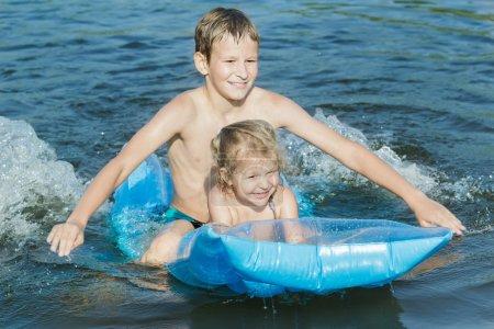 Siblings having fun during summer sea bathing with robin egg blue pool air mat outdoor