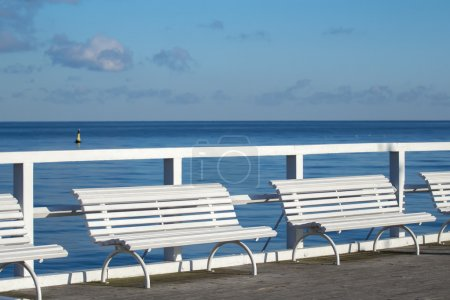 White comfort benches on sea walking pier