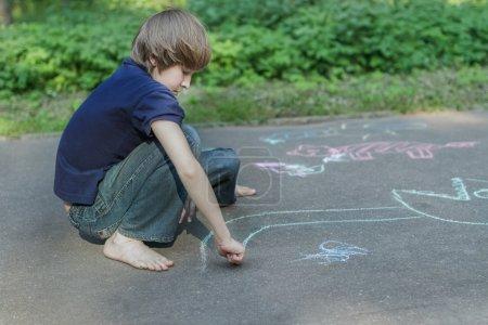 Sidewalk chalk drawings of barefoot teenage boy wearing blue t-shirt and jeans