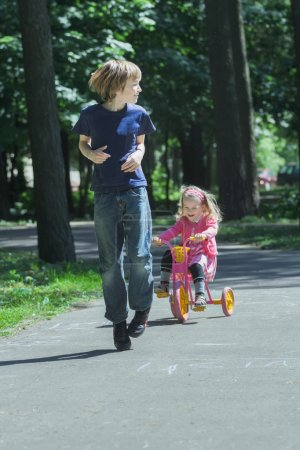 Laughing sibling sister chasing after her brother on pink and yellow kids tricycle