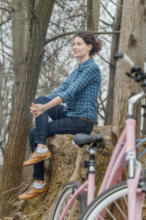 Attractive brunette girl sitting on huge old tree stump with pink vintage bike at foreground