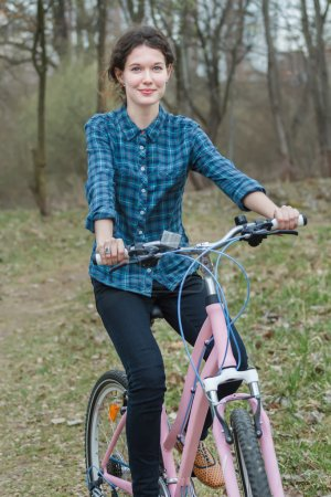 Happy brunette cyclist riding pink vintage bicycle in old park