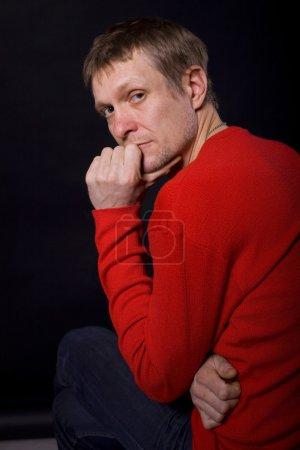 Photo pour Portrait en studio de l'homme réfléchi de quarante ans sur fond noir - image libre de droit