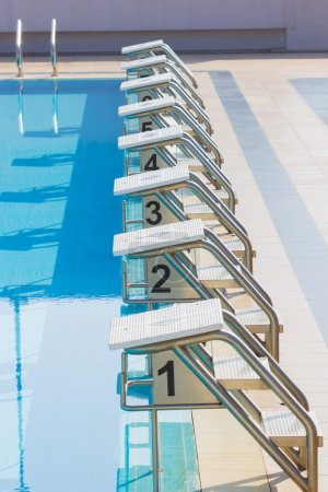 A Row Of Swimming Pool Starting Blocks At The pool Edge. Vertica