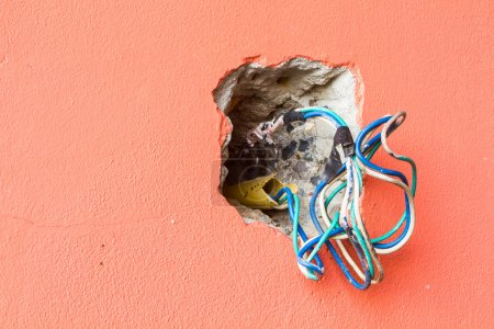 crack hole wall with electric colored wires, copyspace on the le