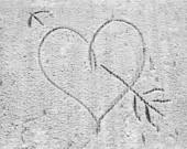 The heart pierced with an arrow, drawn on snow.