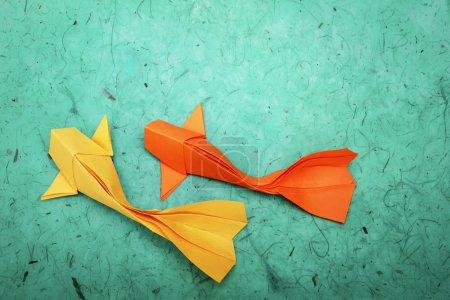 Photo pour Origami papier groupe de poissons rouges sur un fond d'eau verte - image libre de droit