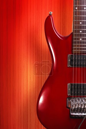 Photo for Red electric rock musical instrument guitar on yellow background - Royalty Free Image