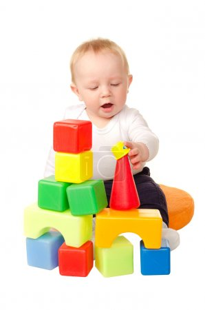 Cheerful baby boy playing with colorful blocks