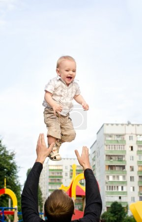 Photo for Daddy tossing his infant son up on sky background in city outdoors - Royalty Free Image