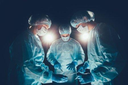 Photo pour Équipe médicale à l'hôpital effectuant l'opération. Groupe de chirurgiens au travail en salle d'opération. soins de santé Lumière vive dans le cadre effet artistique - image libre de droit