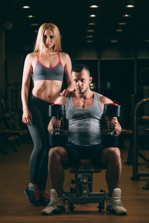 beautiful young sporty sexy couple showing muscle and workout in gym dumbbell