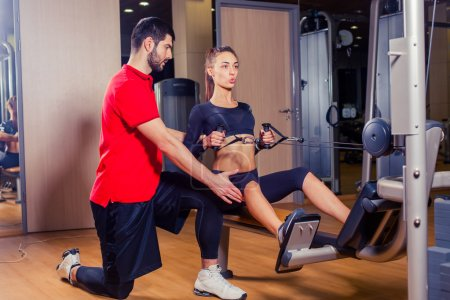 Personal trainer working with his client in gym