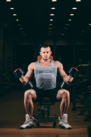 sport, bodybuilding, weightlifting, lifestyle and people concept - young man with dumbbells flexing muscles in gym