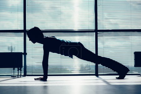 fitness, sport, training and people concept - smiling woman doing abdominal exercises on mat in gym contour of the body against the window