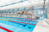 Mladý svalnatý plavec skákání ze startovní blok v bazénu