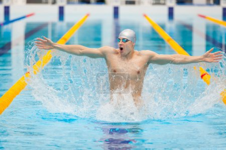 dynamic and fit swimmer in cap breathing performing jumping out the water, concept of victory, freedom, happiness, healthy lifestyle