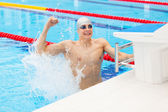 Young male swimmer celebrating victory in the swimming pool