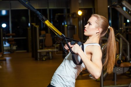 Young attractive woman does crossfit push ups with trx fitness straps in the gyms studio
