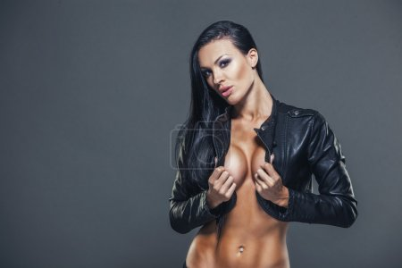 Beautiful girl sexy breasts in unbuttoned jacket with long black hair
