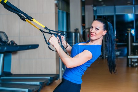 Young attractive woman training with htrx fitness straps in the gyms studio