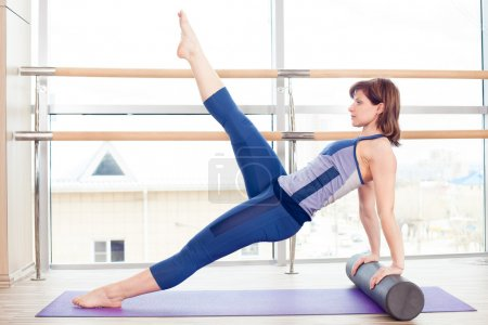 fitness, sport, training and lifestyle concept -  woman doing pilates on the floor with foam roller